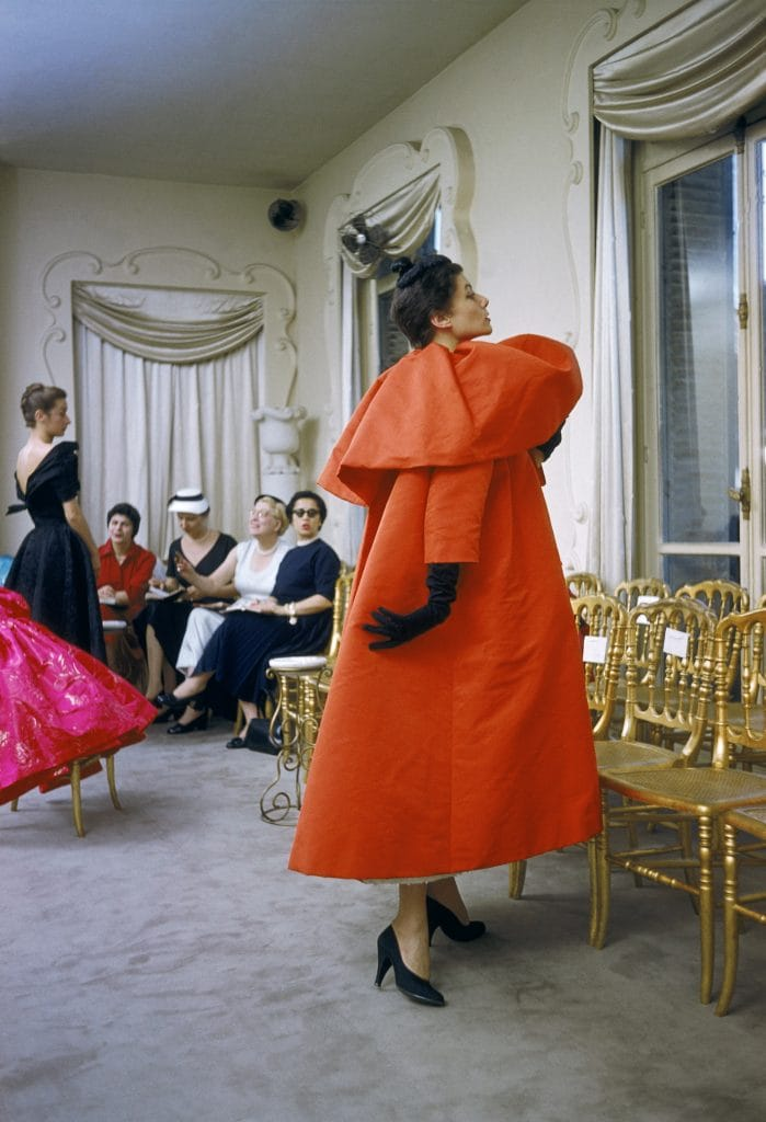 Model_wearing_Balenciaga_orange_coat_as_I._Magnin_buyers_inspect_a_dinner_outfit_in_the_background_Paris_France_1954__Mark_Shaw_mptvimages